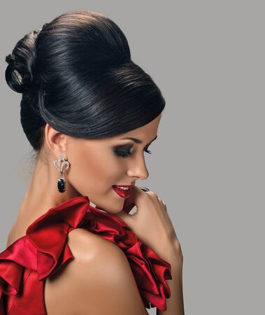 beautiful woman with dark tanned skin and black hair in fashion hairstyle and earrings. photo