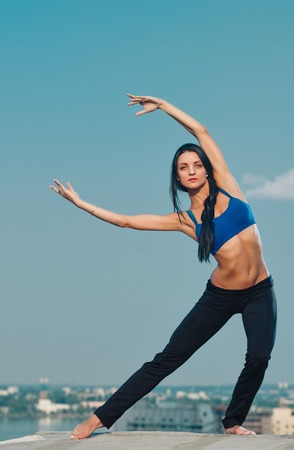 housetop: yoga fitness and lifestyle concept - woman doing sports outdoors on the house-top Stock Photo