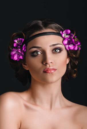 Beauty portrait of young woman with purple floral wreath over dark background photo