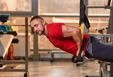 Crossfit fitness TRX push ups man workout at gym photo