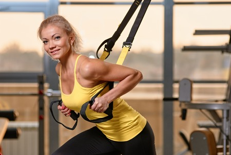 Young attractive woman training with htrx fitness straps in the gyms studio photo