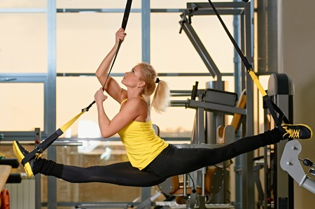 Young attractive woman does splits crossfit stretching with trx fitness straps in the gyms studio Foto de archivo