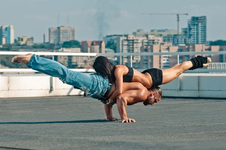 Couple yoga of woman and man on the house-top