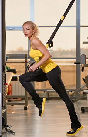 Young attractive woman training with htrx fitness straps in the gyms studio Фото со стока