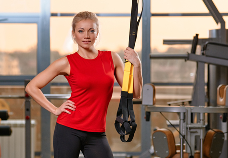 Athletic woman with functional loops for training at gym studio photo