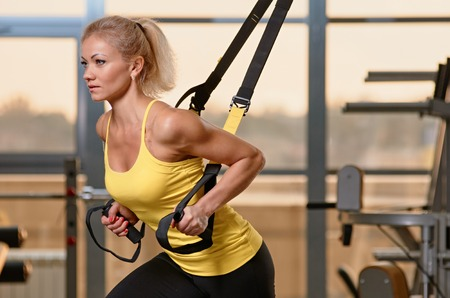 Young attractive woman training with htrx fitness straps in the gyms studio Foto de archivo