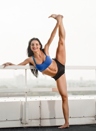 splits: Photo of a slim woman dancer training and doing standing splits outdoor Stock Photo