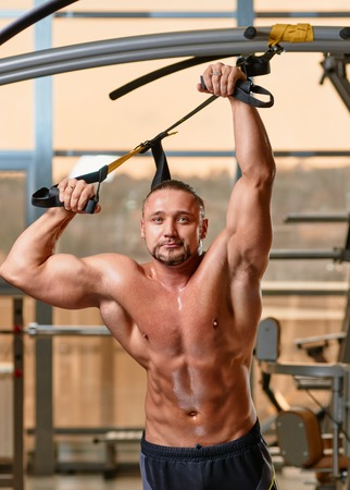 Crossfit fitness TRX man portrait workout at gym photo