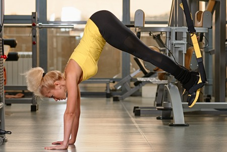 Young woman doing push-ups while legs hanging on elastic rope