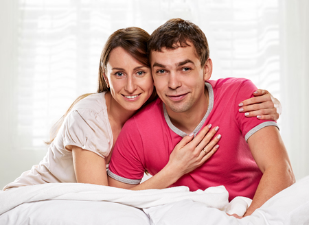 Happy smiling couple laying laughing in bed photo