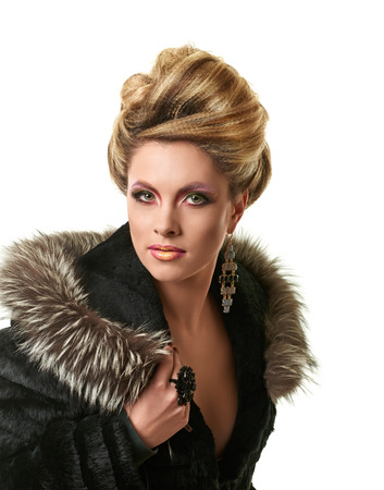 Glamour lady portrait in luxury fur coat. Beautiful model girl with fashion makeup and hairstyle.