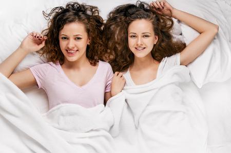 mujeres felices: dos hermosas j�venes amigos de la chica en la cama