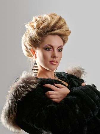 Glamour lady portrait in luxury fur coat. Beautiful model girl with fashion makeup and hairstyle. photo