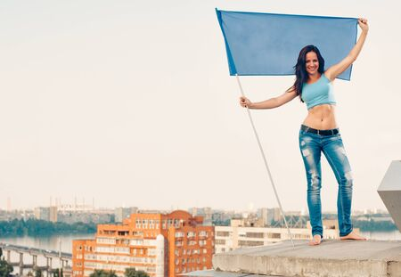 housetop: yoga fitness woman relax outdoors on the house-top with flag