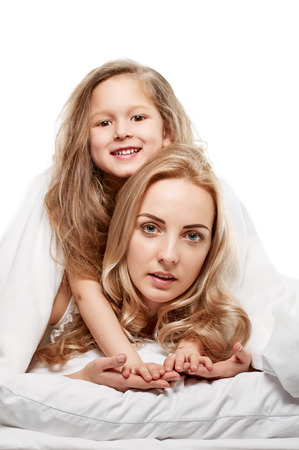 Portrait of a joyful mother and her daughter in the bed on white photo