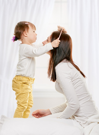 mam: daughter brushing her mam hair at home on light window background