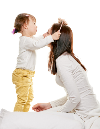 mam: daughter brushing her mam hair at home on white background