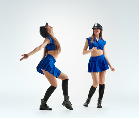 sexy police: dancing Sexy twins girl in police uniform on light background