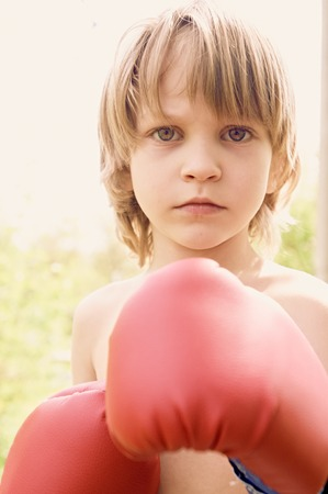 boxing boy: The boy in boxing gloves against a light background, close up portrait