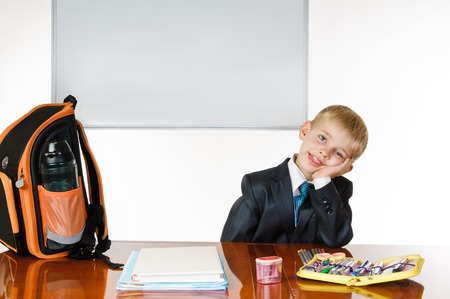 satchel: Young schoolboy with desk satchel and blackboard on white background. thinking