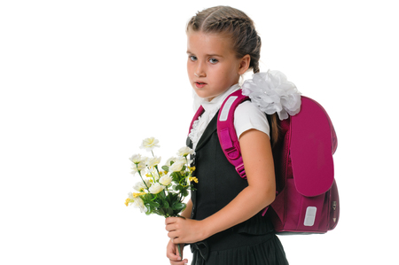 Little schoolgirl with a backpack and flowers isolated over white photo