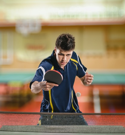 table tennis: young sports man tennis-player in play on sport club background