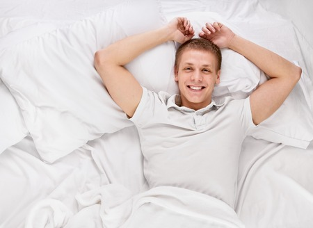 Young handsome happy man waking up on bed, top view