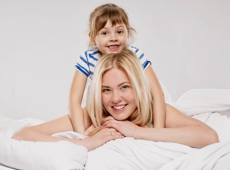 beautiful mom: Portrait of a joyful mother and her little daughter in the bed on light grey background Stock Photo