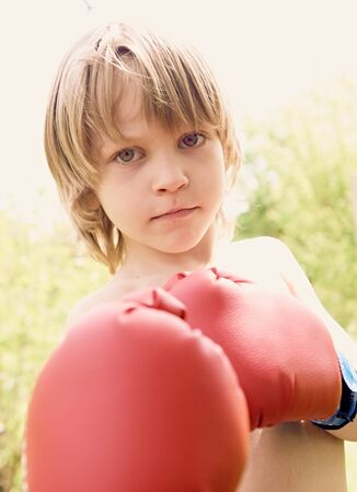 pugilist: The boy in boxing gloves against a light background, close up portrait