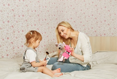 adult toys: happy mother with her child in room. playing on sofa with toys Stock Photo