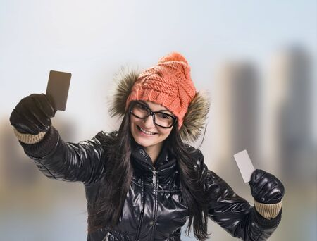 black gloves: portrait of young smiling woman holding credit card on sunny city background. wearing in winter cap, spectacles , jacket, black gloves