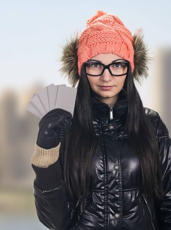 black gloves: portrait of young smiling woman holding credit cards like a fan on sunny city background. wearing in winter cap, spectacles , jacket, black gloves