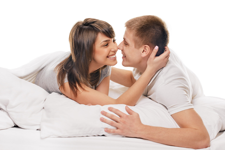 romance bed: Happy smiling couple laying laughing in bed on white background Stock Photo