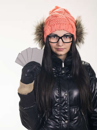 black gloves: portrait of young smiling woman holding credit cards like a fan on grey background. wearing in winter cap, spectacles , jacket, black gloves