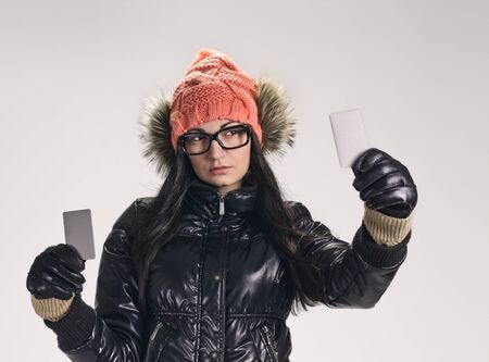 black gloves: portrait of young smiling woman holding credit card on grey background. wearing in winter cap, spectacles , jacket, black gloves Stock Photo