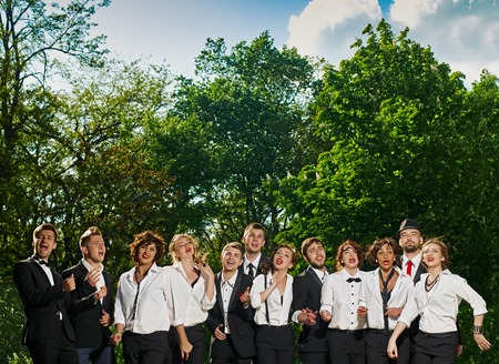 vocals: singing cheerful friends dressed tuxedo in the summer city. green trees are background. they are vocals group