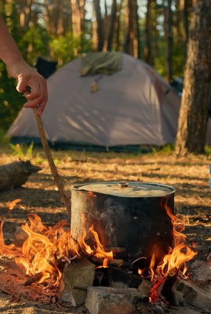 soup kettle: Tourist kettle on camp fire with tent on background. hand with stick about fire. Stock Photo