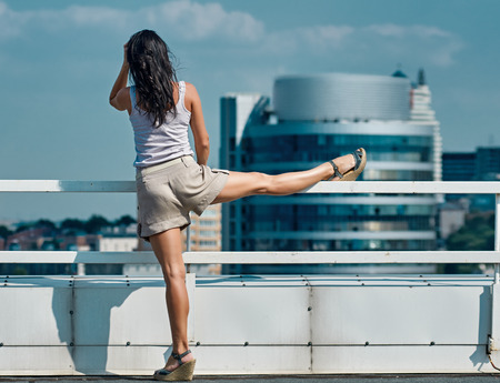 housetop: sport, fitness, exercise and lifestyle concept - woman doing sports outdoors on house-top in the city