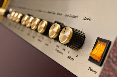 amp: brown Electric guitar amplifier button on white background
