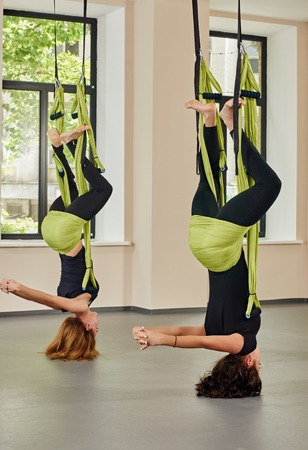 hang body: Young women making antigravity yoga exercises. green hammocks Stock Photo