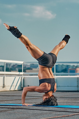 housetop: woman doing headstand in outdoor house-top city Stock Photo
