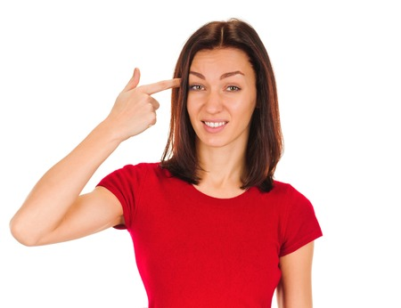 insulting: young woman gesturing with her finger against her temple. Isolated on white background Stock Photo