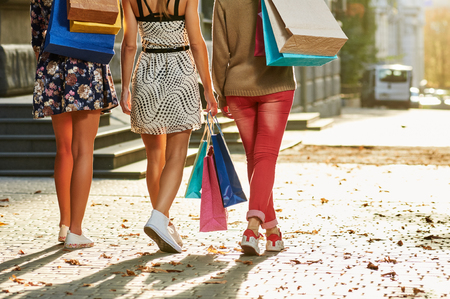 girls women friends with sexy legs walking. from back. with shopping bags