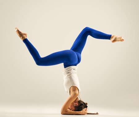 headstand: Sporty girl doing Supported yoga Headstand, studio