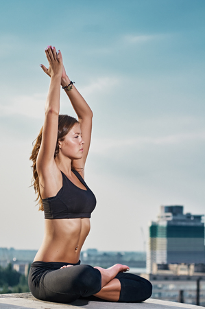 spring training: Yoga and meditation in a modern urbanistic city. Young attractive girl - yoga meditates against modern skyscrapers