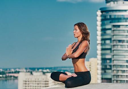 salud y deporte: El yoga y la meditación en una ciudad urbanística moderna. La muchacha atractiva joven - medita yoga contra rascacielos modernos