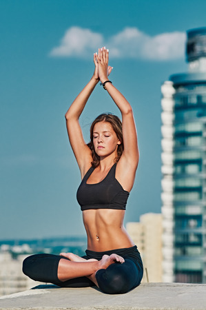 urbanistic: Yoga and meditation in a modern urbanistic city. Young attractive girl - yoga meditates against modern skyscrapers