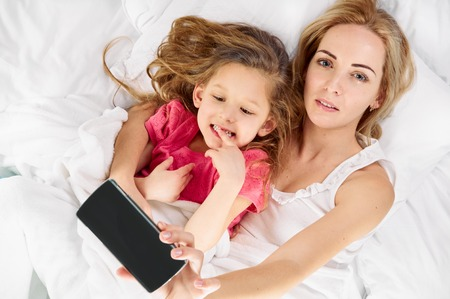 freetime: daughter and mother are happy together. making selfie with smartphone. freetime in bed Stock Photo