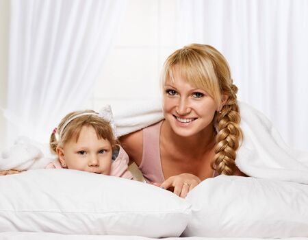 young  family: Young mother hugging her daughter on light window background Stock Photo