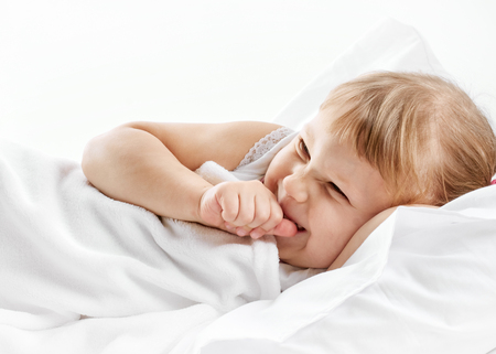 awake: Adorable little girl awaked up in her bed. on white background Stock Photo